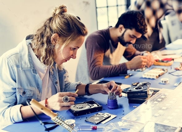 Electrical technicians working on computer parts - Stock Photo - Images