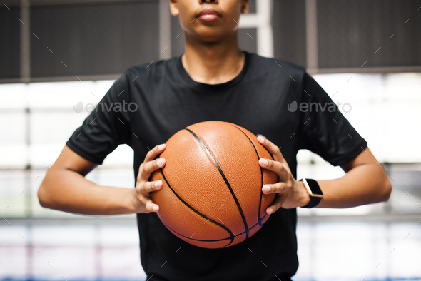 African American teenage boy holding a basketball on the court - Stock Photo - Images