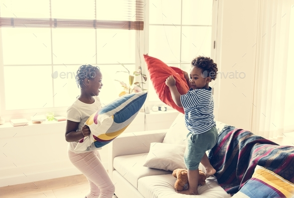 Brother and sister pillow fighting in living room - Stock Photo - Images