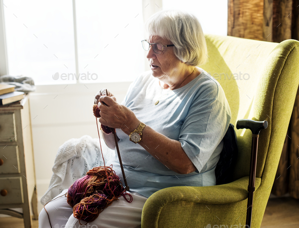 Senior woman knitting for hobby at home - Stock Photo - Images