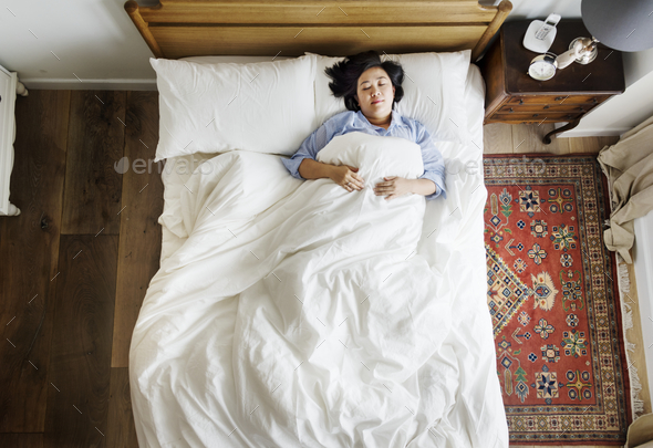 Asian woman on the bed sleeping by herself - Stock Photo - Images