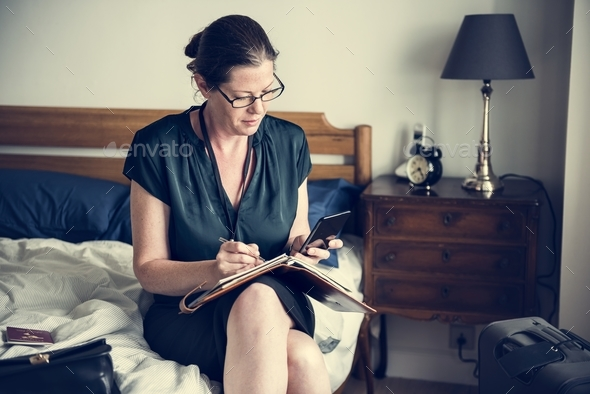 A woman working in bed - Stock Photo - Images