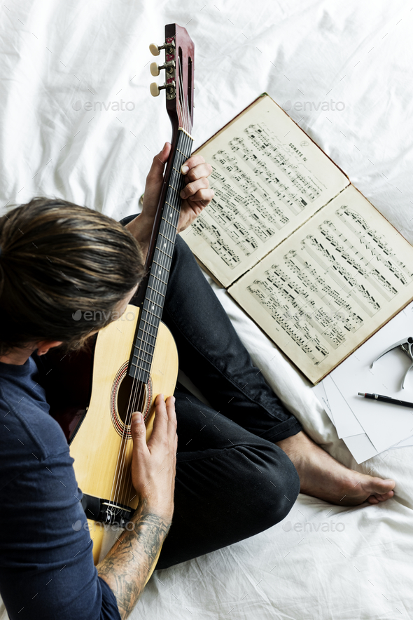 Man Practising notes with guitar - Stock Photo - Images