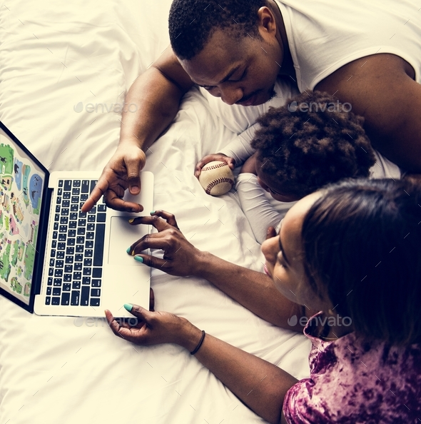 Black family lying on bed using computer laptop together in bedroom - Stock Photo - Images