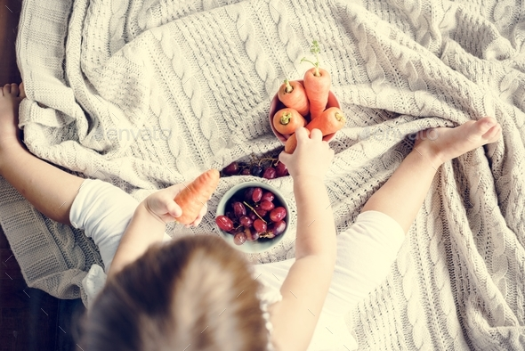 Little girl sitting looking a carrot and grape - Stock Photo - Images
