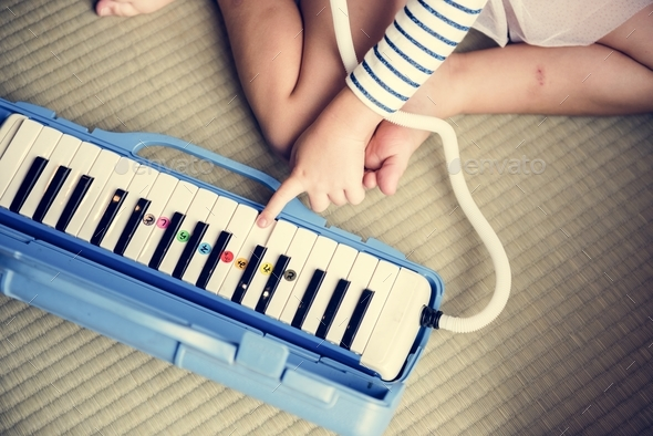 Girl palying piano music toy equipment - Stock Photo - Images