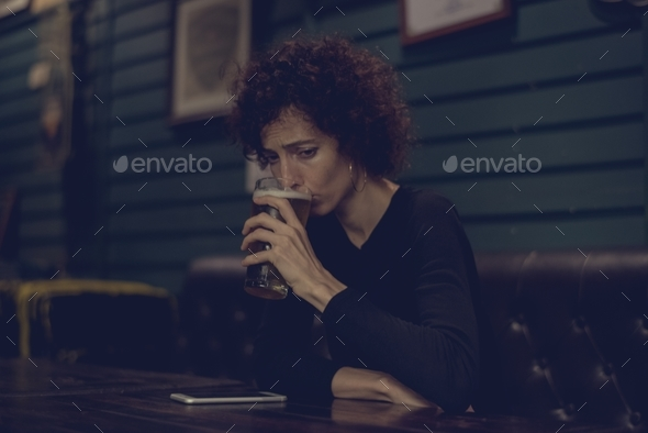 Woman having a beer at a bar - Stock Photo - Images