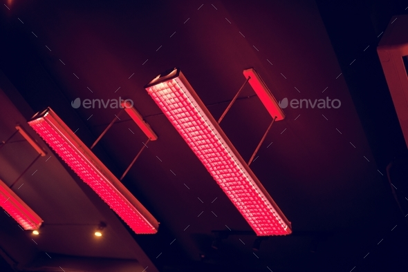 Red fluorescent lamp hanging from the ceiling - Stock Photo - Images