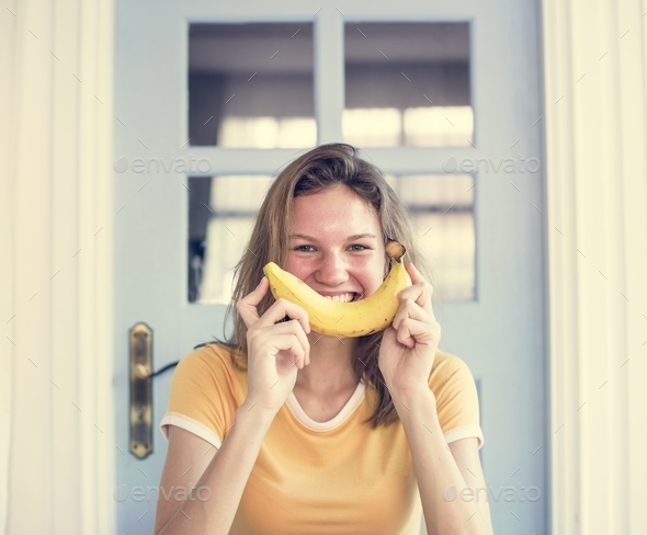 A Caucasian woman with banana and a smile on her face - Stock Photo - Images