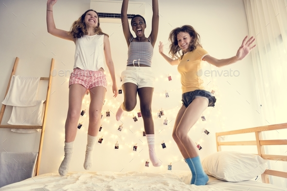 A group of diverse women jumping on bed together - Stock Photo - Images