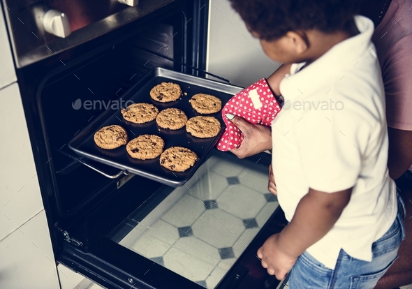 Black kid helping mom baking cookies - Stock Photo - Images