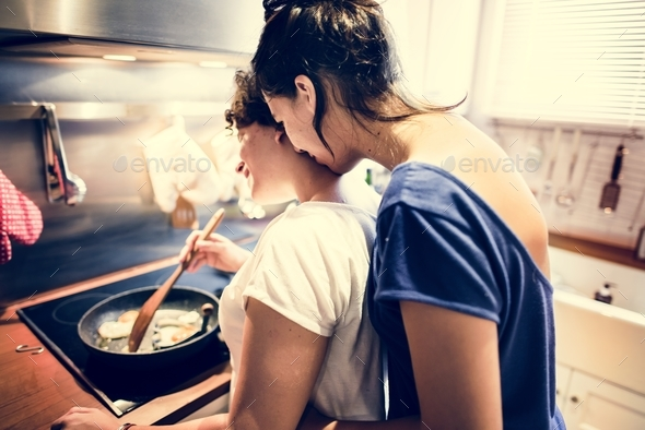 Lesbian couple cooking in the kitchen together - Stock Photo - Images