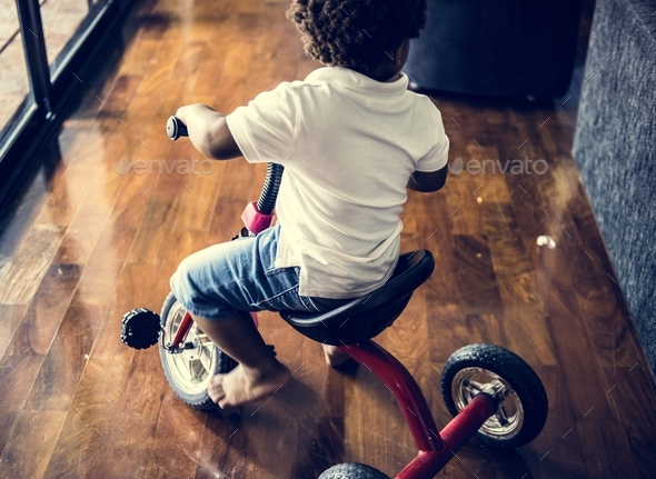 Black kid riding bicycle in the house - Stock Photo - Images