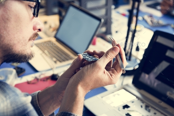 Closeup of hands holding tweezer with computer processor chips - Stock Photo - Images
