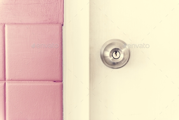 Closeup of stainless steel door knob on white door - Stock Photo - Images