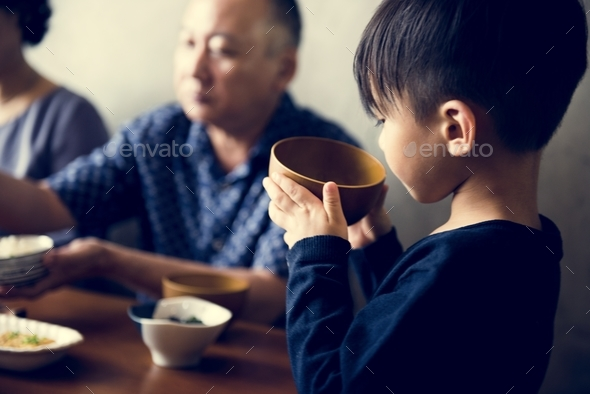 Japanese boy holding a bowl of soup - Stock Photo - Images