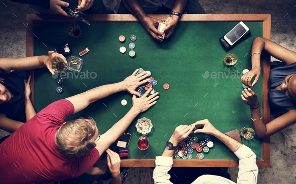 Diverse group playing poker and socialising - Stock Photo - Images