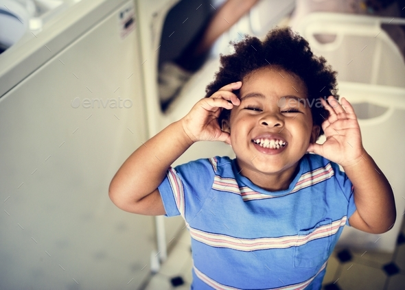 Black kid smiling in the laundry room - Stock Photo - Images