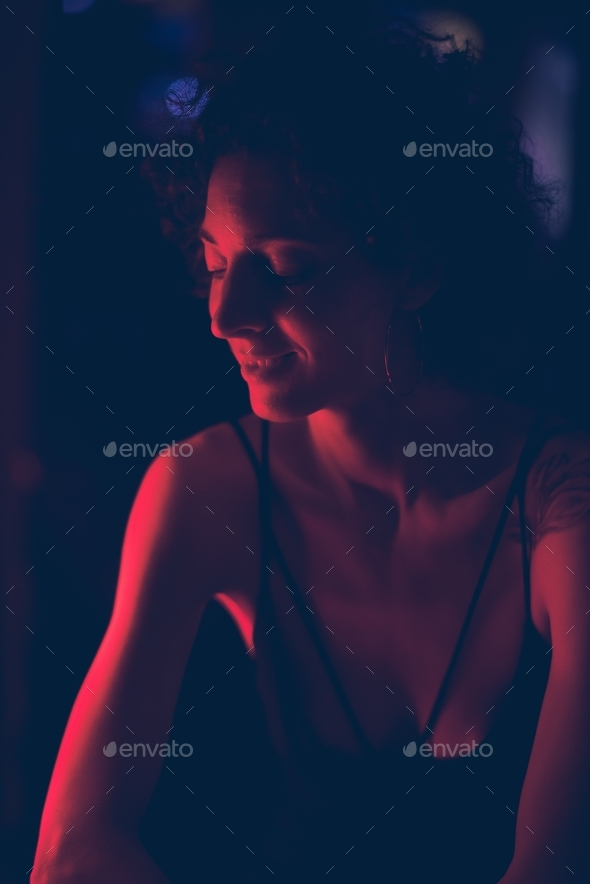 Portrait of a woman in a dark bar - Stock Photo - Images