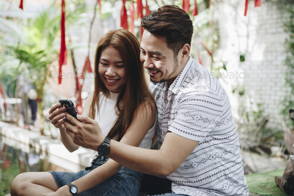 Young couple using a phone together - Stock Photo - Images