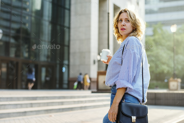 Woman standing with a cup of coffee - Stock Photo - Images