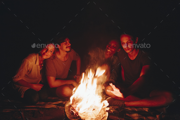 Group of friends sitting around a bonfire at a campsite - Stock Photo - Images