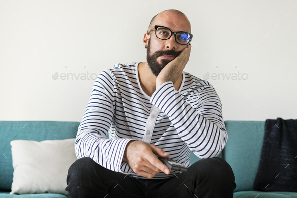 Bored man sitting and watching TV - Stock Photo - Images