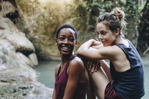 Two friends relaxing by a waterfall - Stock Photo - Images