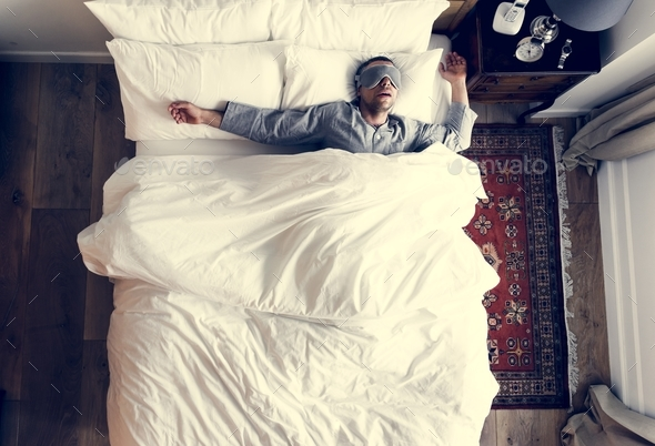 Man on bed sleeping with an eye cover - Stock Photo - Images