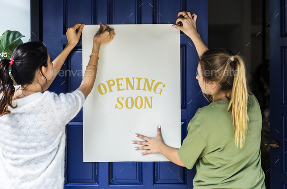 Women putting on store opening soon sign - Stock Photo - Images
