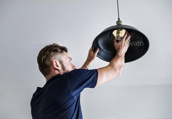 Man changing lightbulb - Stock Photo - Images