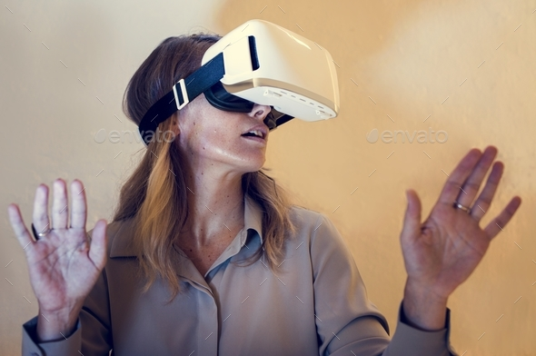 Woman using virtual reality gadget for entertainment - Stock Photo - Images