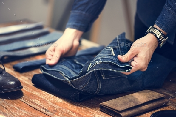 Man folding jeans - Stock Photo - Images