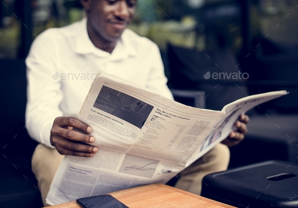 African descent man sitting reading a newspaper outdoor - Stock Photo - Images