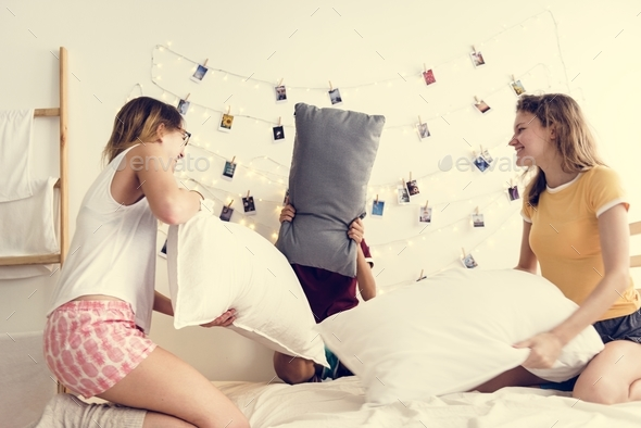 A diverse group of women playing pillow fight on bed together - Stock Photo - Images