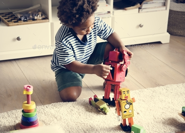 Black boy playing robot at home - Stock Photo - Images