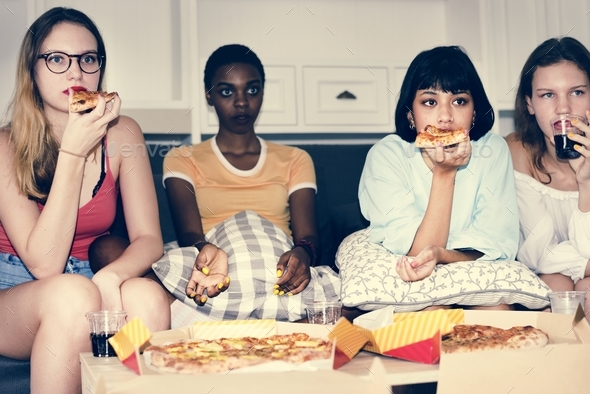 A diverse group of women sitting on the couch and eating pizza together - Stock Photo - Images