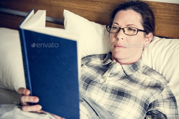 A woman reading in bed - Stock Photo - Images