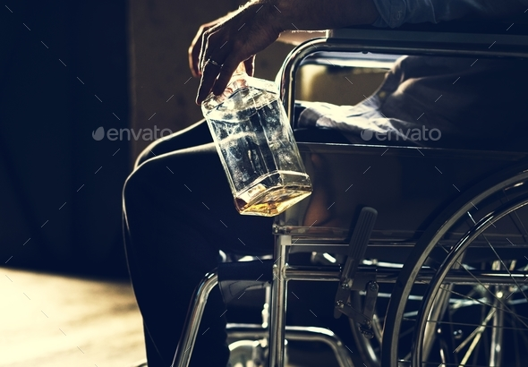 Alcoholic man sitting in a wheelchair - Stock Photo - Images