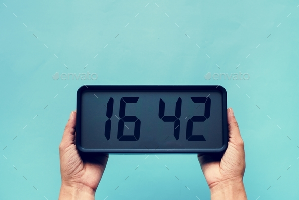 Hands holding digital clock isolated on background - Stock Photo - Images