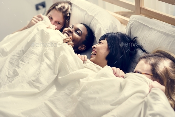 Group of diverse women lying on bed together under the blanket - Stock Photo - Images