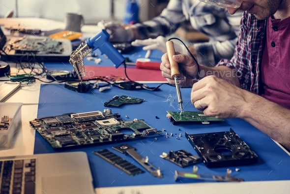 Hand soldering tin on electronics circuit board - Stock Photo - Images