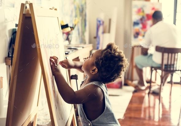Black kid enjoying his painting - Stock Photo - Images