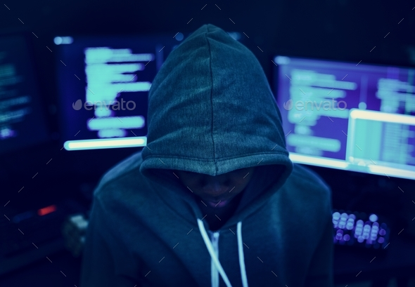 Hacker wearing a hoody with computers in the background - Stock Photo - Images
