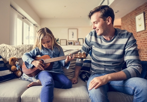 Young Caucasian girl playing ukulele - Stock Photo - Images