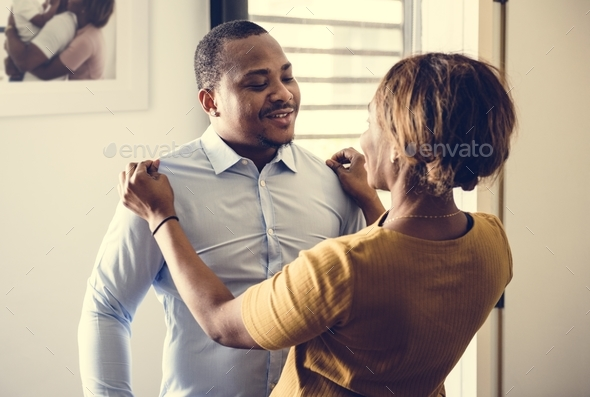 Black wife helping husband dress up for work - Stock Photo - Images