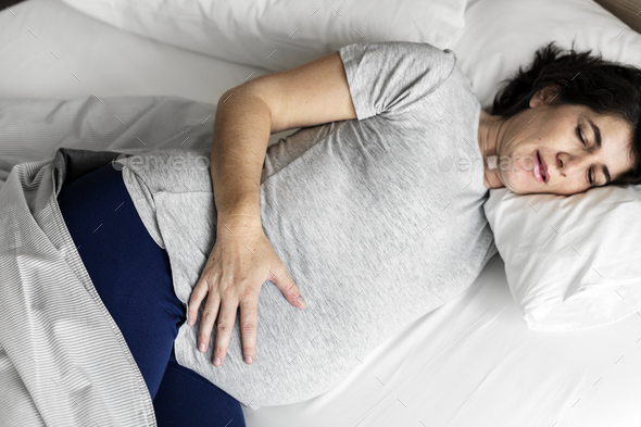 Pregnant woman sleeping on the bed - Stock Photo - Images