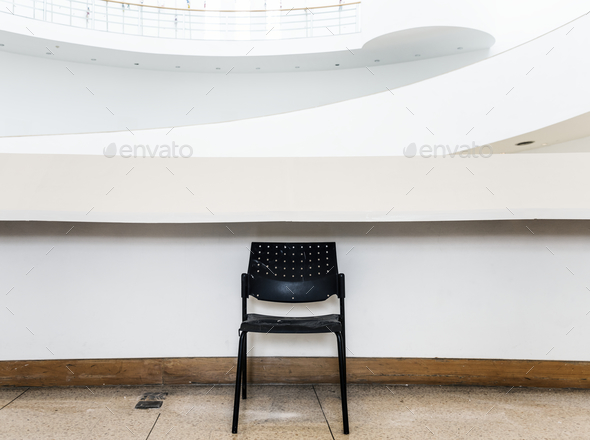 An abandoned black chair in a building - Stock Photo - Images