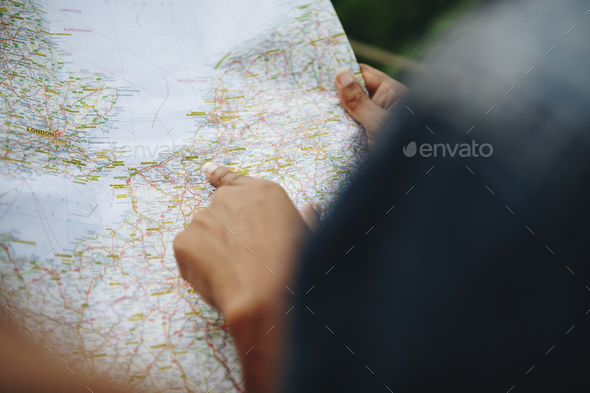 Two women friends looking at a map together travel and teamwork concept - Stock Photo - Images