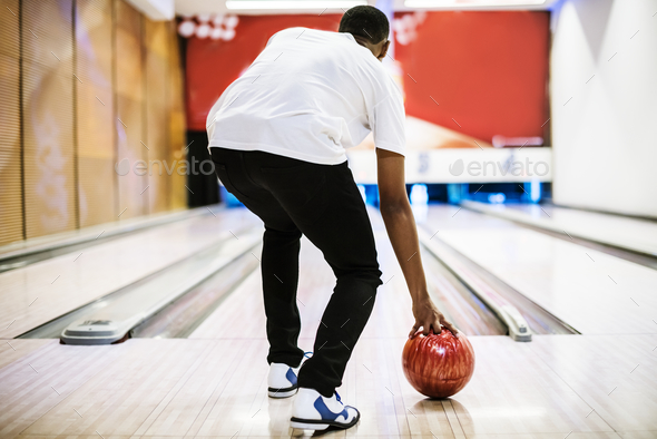 Boy about to roll a bowling ball hobby and leisure concept - Stock Photo - Images